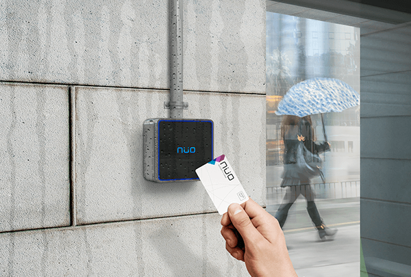 Imagen de una mano acercando una tarjeta a una lector de control de acceso en exterior, un dia lluvioso
