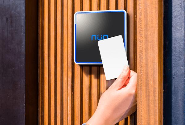 Mano acercando una tarjeta de proximidad a una lector de control de acceso de la marca NÜO